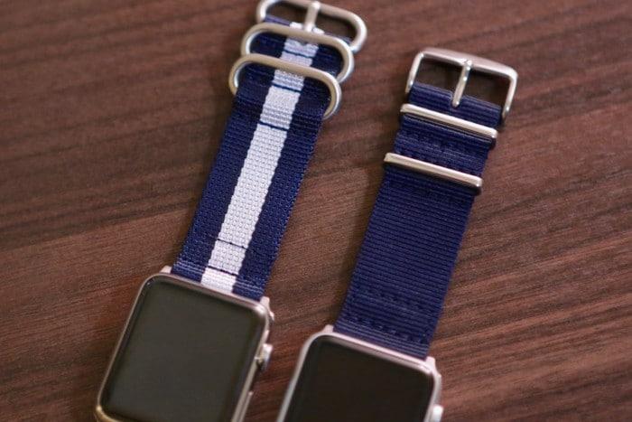 Kép: A két NATO szíj csatjainak összehasonlítása: a kék-fehér-kék csíkos lekerekített csattal és bújtatókkal rendelkezik, a sima kék pedig szögletesekkel.