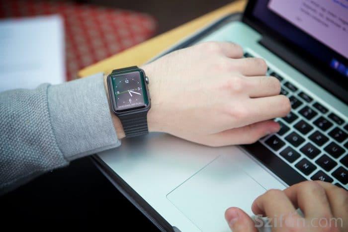 Kép: Fekete Apple Watch Sport, fekete Leather Loop szíjjal, analóg óraszámlappal.