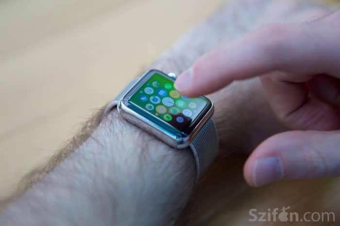 Kép: Apple Watch közelről, mutatóujjal majdnem rányomva az egyik ikonra a főképernyőjén.