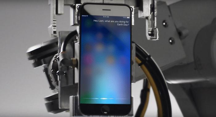 Borítókép: Liam, a robot egy ártatlanul várakozó iPhone-t tart a robotkarjában, amin Siri kérdezi tőle, hogy mivel tölti a Föld napját.