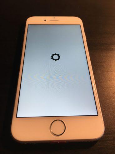 Kép: Az iPhone 6 prototípus szoftverének betöltődési képernyője, egy fekete fogaskerék van a fehér képernyő közepén az alma logó helyett.