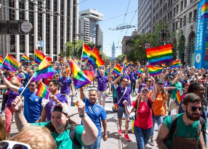 Borítókép: Fotó a San Franciscó-i Pride felvonulásról, tele szivárványszín-csíkos zászlókat lobogtató emberekkel.