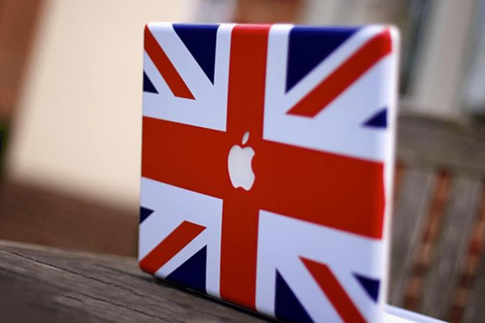 Borítókép: Brit zászlós matricával befedett MacBook, ahol a zászló közepén a fehér alma szabadon van hagyva.