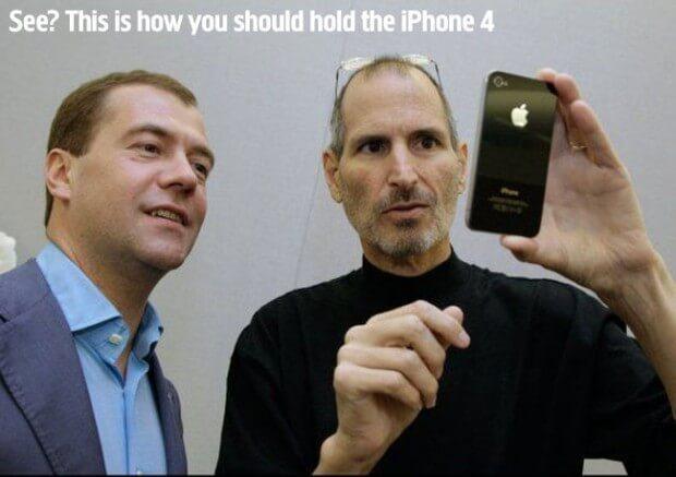 """Steve Jobs Dimitri Medvegyevnek mutatja az iPhone 4-et, amit mindössze 4 ujjával tart a készülék tetejét és alját fogva, a képen felirattal: """"See? This is how you should hold the iPhone 4. (Látja? Na így kell fogni az iPhone 4-et!)""""."""