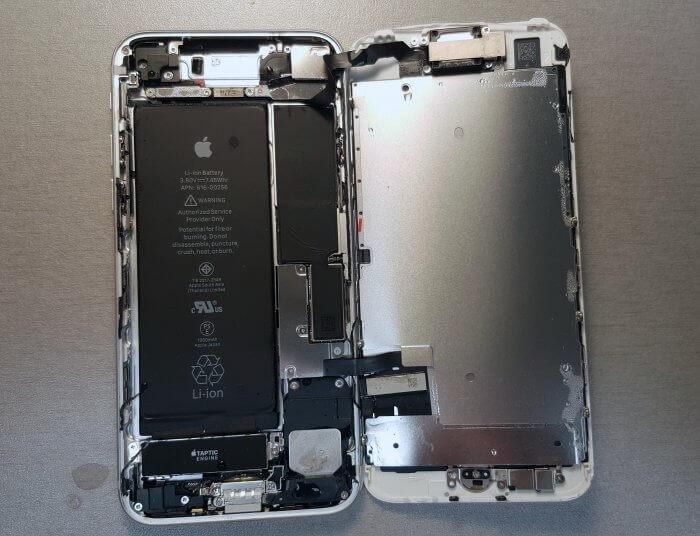 Beázott iPhone 7, a szétnyitott készülékben egyértelműen látszanak a bejutott folyadék cseppjei.