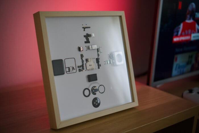 Egy 38mm-es, alumínium tokozású, első generációs Apple Watch képkeretben, íróasztalon.