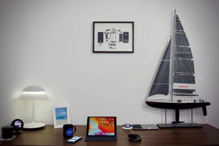 Egy fekete iPhone 4 képkeretben, íróasztal fölött a falon.