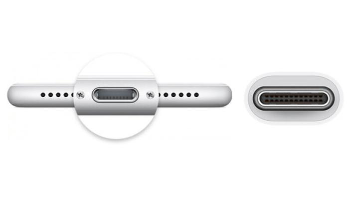 Egy iPhone alsó része a Lightning-aljzattal, és egy USB-C kábel vége.